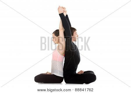 Yogi Couple Doing Exercises For Spine And Shoulders In Lotus Position