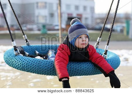 Child Lying On A Swing