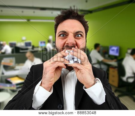 Angry Businessman While Eating Balled Paper In Office.