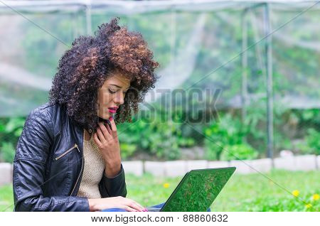 exotic beautiful young girl using laptop in the garden