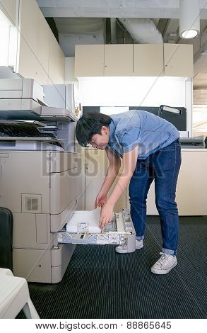 Young Woman Inserting Paper In Laser Printer Cartridge With An Office Background