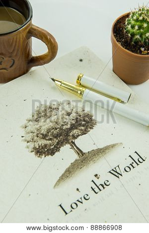 Earth Day concept, Love the world coffee cup and pen on the table.
