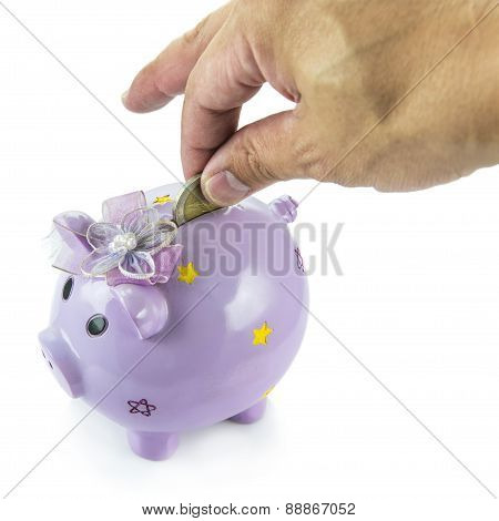 Saving, male hand putting a money into piggy bank isolated on white background.