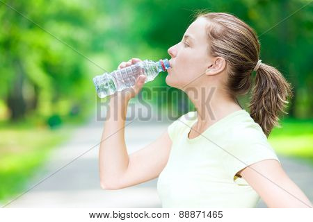 Woman drinking cold mineral water from a bottle after fitness ex