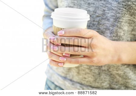 Female hands with paper cup of coffee outdoors, closeup