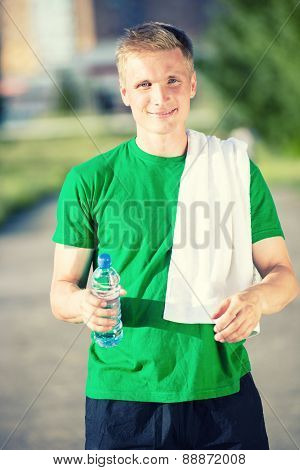 Tired man with white towel drinking water from a plastic bottle
