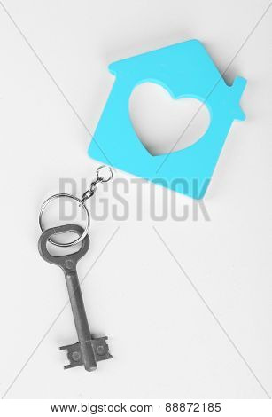 Toy house with key isolated on white