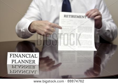 Financial Planner sitting at desk holding Retirement document