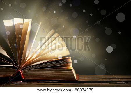 Open book on shiny dark background