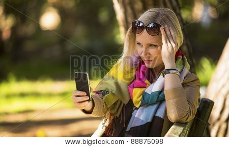 Young fashion woman sitting in the Park is typing on a smartphone.