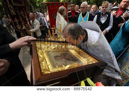 PRAGUE, CZECH REPUBLIC - MAY 28, 2012: Orthodox priest kisses the miracle-working icon of the Virgin Mary in front of the Dormition Church at the Olsany Cemetery in Prague, Czech Republic.