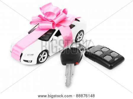 Keys and car with pink bow as present isolated on white