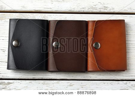 Three hand made leather man wallets on white wooden background