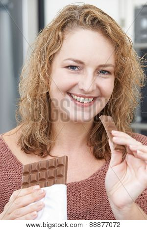 Smiling Plus Size Woman Eating Bar Of Chocolate