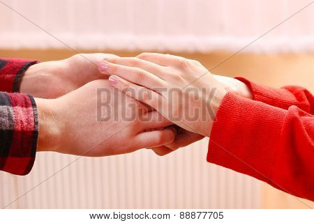 Couple holding hands on light blurred background