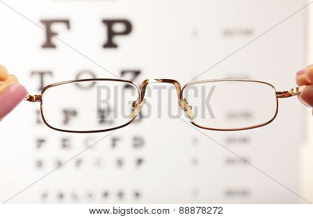 Eye glasses in female hands on eyesight test chart background