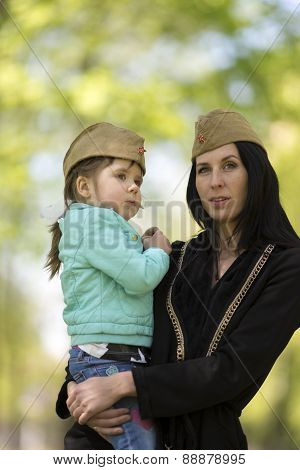 Young woman with her daughter in her arms in front forage caps