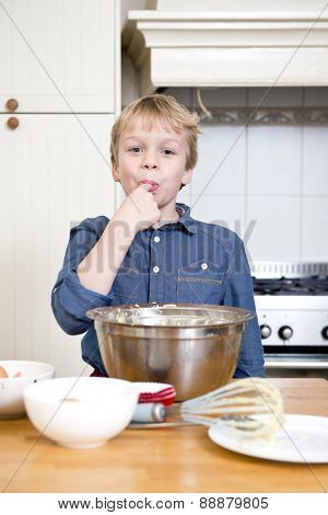 Young child with sweet teeth, tasting batter from a bowl in a kitchen, wearing a blue shirt, with bowls, plates, and a whisk on the kitchen counter in front of him