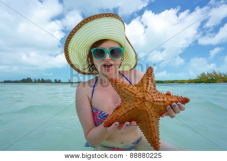 Portrait of young beautiful woman in bikini posing with sea-star on sea background