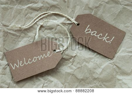 Two Beige Labels With Text Welcome Back Paper Background