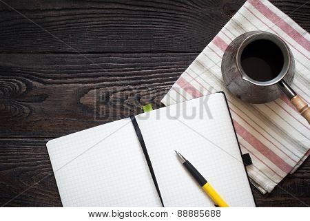 Notebook, pen and coffee pot on the table