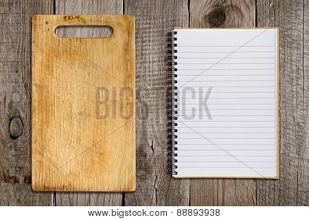 Chopping Board And Recipe Book On Old Wooden Background