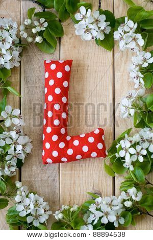 Natural Wooden Background With White Flowers Fruit Tree. In The Middle Is The Letter L, Is Made Of R