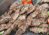 image of buffet  - Closeup detail of grilled lamb kofta meat on display at an oriental restaurant buffet