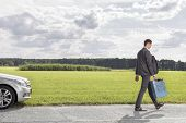 stock photo of leaving  - Full length of young businessman with gas can leaving broken down car at countryside - JPG