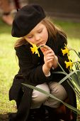 pic of overcoats  - A pretty young blonde girl of four dressed in a brown overcoat trousers and beret is holding a yellow daffodil with one hand and stroking it with the other - JPG