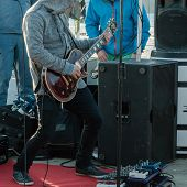 picture of guitarists  - hoodie guitarist playing electrical guitar on a concert - JPG