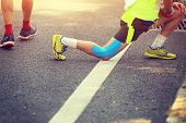 picture of stretching  - closeup of marathon runner stretching legs on road - JPG