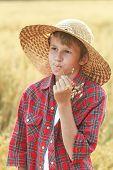 stock photo of oats  - Careless teenage farm boy in wide - JPG