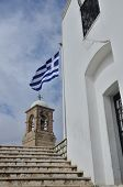 stock photo of chapels  - A view of the Greek flag flying outside a small hilltop chapel - JPG