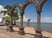 stock photo of malecon  - A row of architectural columns framing an angel statue - JPG