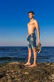 pic of nearly nude  - Attractive handsome sexy naked young man on rock near the sea water with shoes in hand - JPG