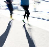 stock photo of jogger  - Two back lit joggers in blurred motion in bright sunshine casting long shadows - JPG