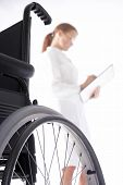 stock photo of rollator  - doctor is looking at the card of the patient and a wheelchair is in the front - JPG