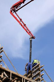 stock photo of boom-truck  - Builder worker with tube from truck mounted concrete pump pouring cement into formwork reinforcement - JPG
