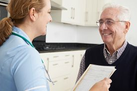 foto of nursing  - Nurse Discussing Medical Record With Senior Male Patient - JPG