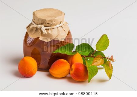 Apricot Jam In A Glass Jar With Ripe Bright Apricots On A White Background