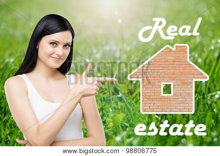 Brunette Real Estate Agent Is Pointing Out The House For Sale. Green Grass Background.