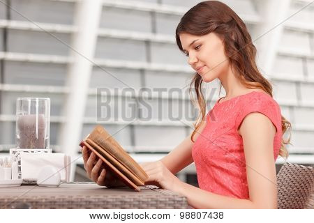 Pretty young woman reading in cafe
