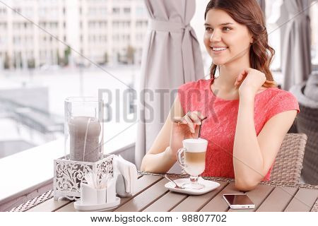 Pretty woman with latte in cafeteria