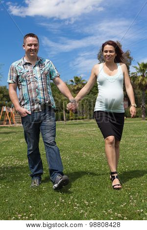 Pregnant Couple Walking Outdoors