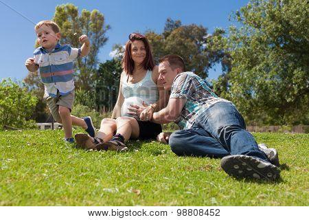 Family Expecting Baby Enjoying Sunny Day