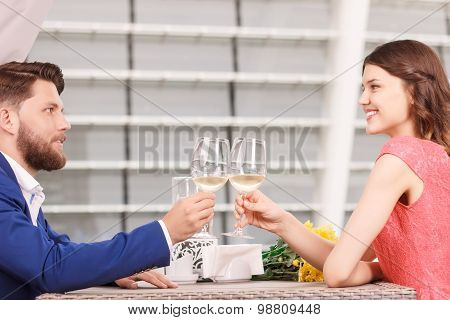Young man and woman clinking glasses in cafe