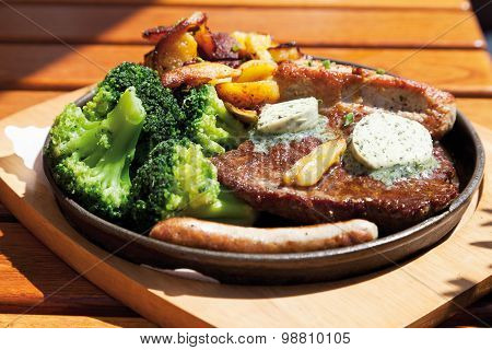 Close Up Of Gourmand Pan With Roasted Meat,herbed Butter,fried Potatoes And Broccoli