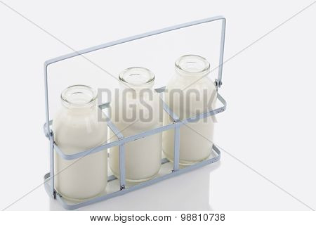Close Up Of Milk Bottles In Rack On White Background