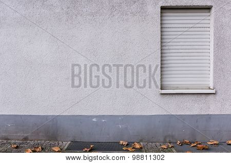 Outside Wall, Closed Window, Aged Stucco Plaster And Gray Foundation